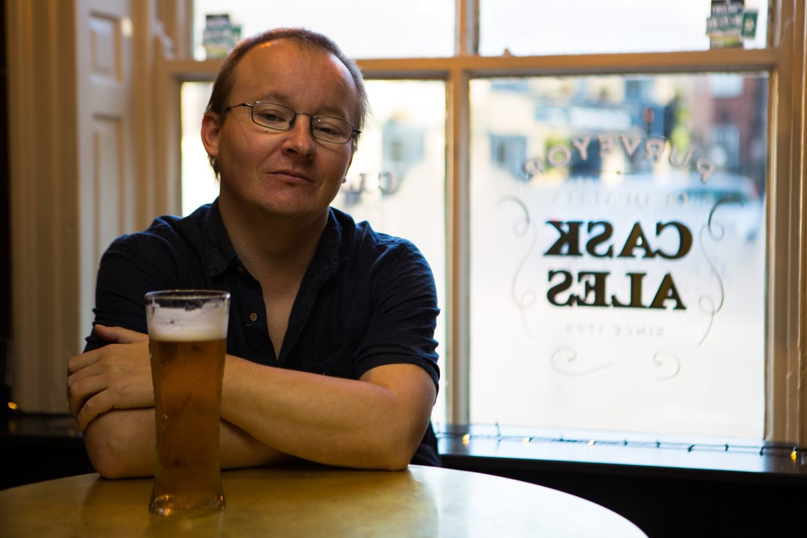 Joe Williams sitting in a pub with a pint. Photo by Joanna Sedgwick.